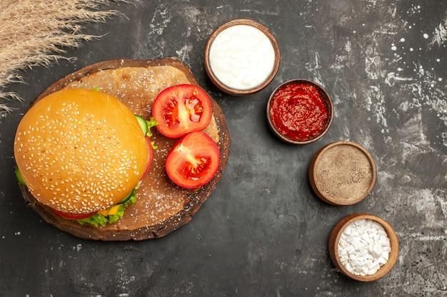 Hambúrguer de carne com queijo e temperos na superfície escura, sanduíche de pão e batata frita