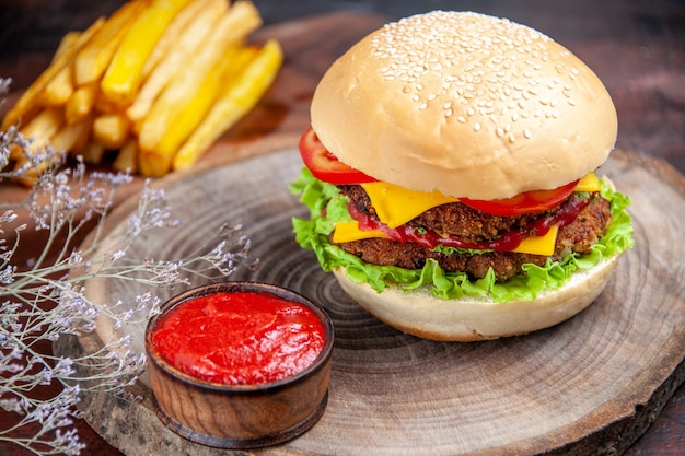 Hambúrguer de carne com queijo, tomate e salada na mesa escura