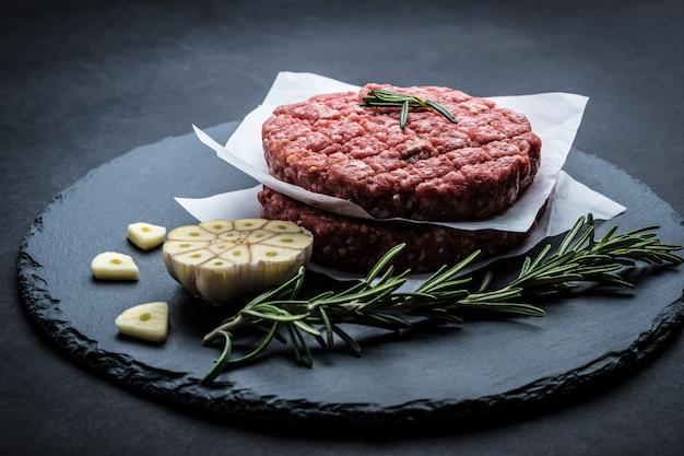Hambúrguer de carne crua com alecrim e alho no fundo escuro para cozinhar