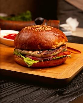 Hambúrguer de carne de frango com fatias de tomate e alface servido com, ketchup e maionese na placa de madeira