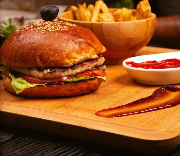 Hambúrguer de carne de frango com tomate e alface dentro e batatas fritas servido com azeitona preta e ketchup em uma bandeja de madeira