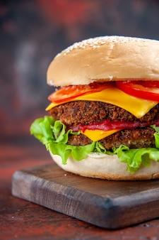 Hambúrguer de carne de frente com salada de queijo e tomate no fundo escuro