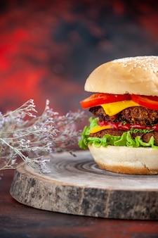 Hambúrguer de carne de frente com tomate queijo e salada em fundo escuro
