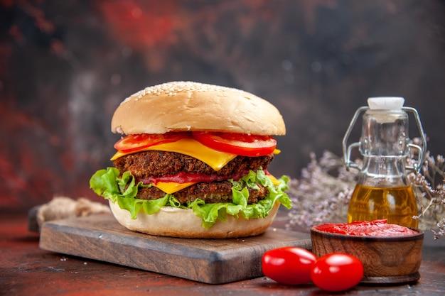 Hambúrguer de carne de frente com tomate, queijo e salada em fundo escuro