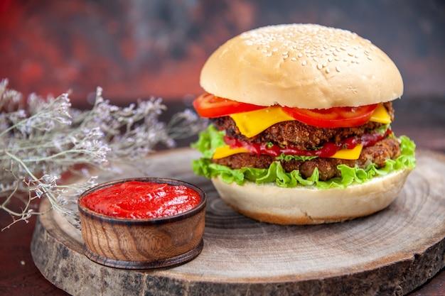 Hambúrguer de carne de frente com tomate queijo e salada no chão escuro