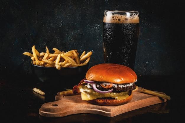 Hambúrguer de carne e queijo fresco com batatas fritas e copo de cerveja de gengibre escuro, em azul escuro, copyspace