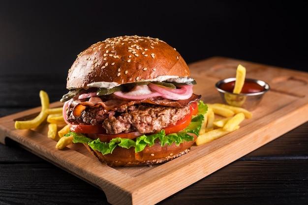 Hambúrguer de carne em uma placa de madeira com batatas fritas