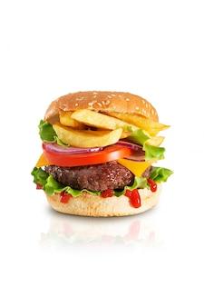 Hambúrguer de carne fresca e suculenta com ketchup pingando e batatas fritas isoladas no fundo branco com reflexão