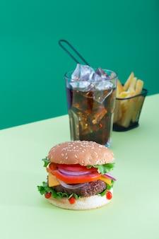 Hambúrguer de carne fresca e suculento colocado em um fundo verde criativo com batatas e bebida, orientação vertical isométrica