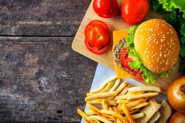 Hambúrguer de carne grelhada com legumes na mesa de madeira, com luz