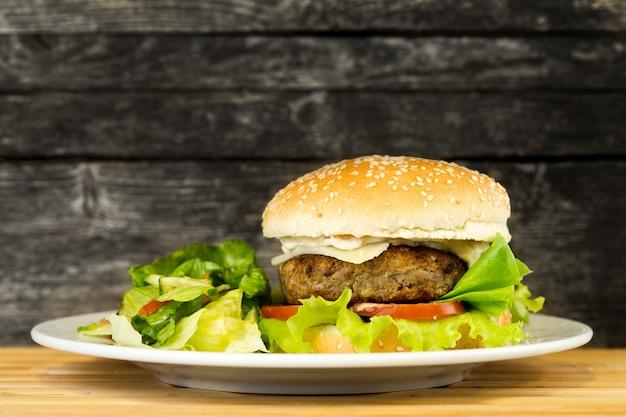 Hambúrguer de carne grelhada delicous em fundo rústico