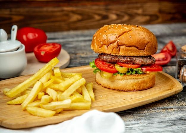 Hambúrguer de carne na placa de madeira tomate alface batatas fritas vista lateral