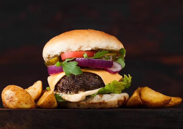 Hambúrguer de carne orgânica fresca com queijo e molho com legumes e batatas vedges na placa de madeira.