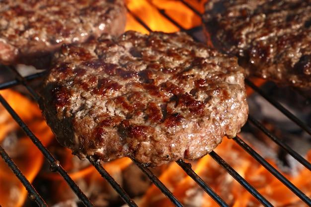 Hambúrguer de carne para hambúrguer na grelha de chamas de churrasco