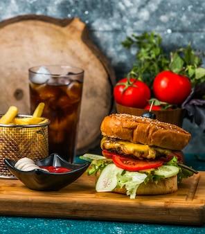 Hambúrguer de carne servido com batata frita, maionese e ketchup