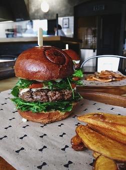 Hambúrguer de carne suculenta com fatias de rúcula e batata