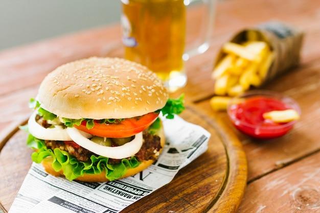 Hambúrguer de close-up de alto ângulo com batatas fritas na placa de madeira