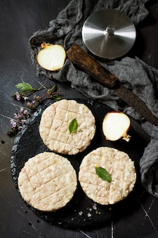 Hambúrguer de costeletas frescas de carne para hambúrgueres caseiros cozinhados com temperos no quadro negro