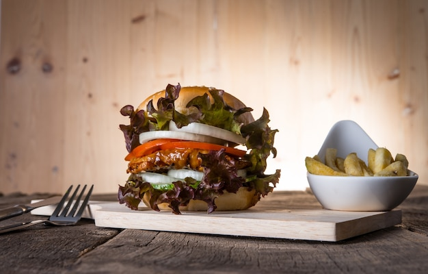 Hambúrguer de frango caseiro com batatas fritas, alface, tomate e cebola na placa de madeira.
