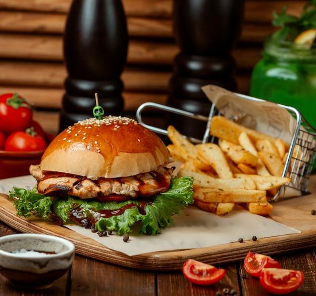 Hambúrguer de frango com batatas fritas na mesa