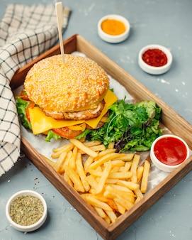 Hambúrguer de frango com batatas fritas na placa de madeira