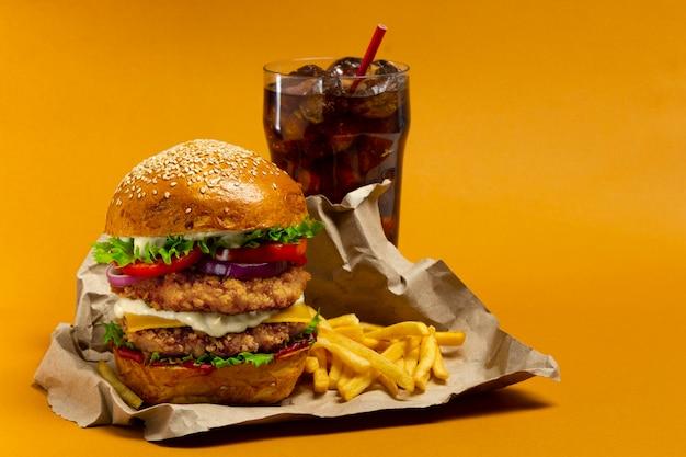Hambúrguer de frango com coca-cola e batata frita em um fundo laranja