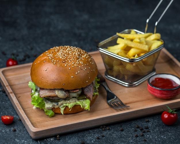 Hambúrguer de frango com ketchup e batatas fritas.