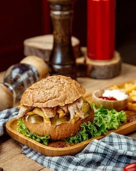 Hambúrguer de frango com ketchup, maionese e batata frita em uma bandeja de madeira