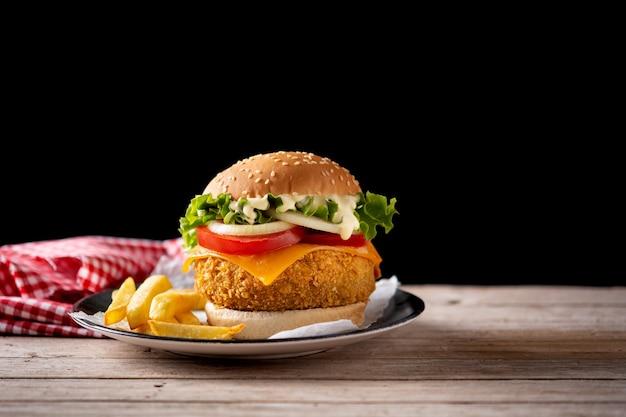 Hambúrguer de frango crocante com queijo e batata frita na mesa de madeira