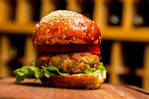 Hambúrguer de frango na vista lateral da placa de madeira