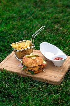 Hambúrguer de frango servido com cesta de batatas fritas, tigela de maionese e ketchup