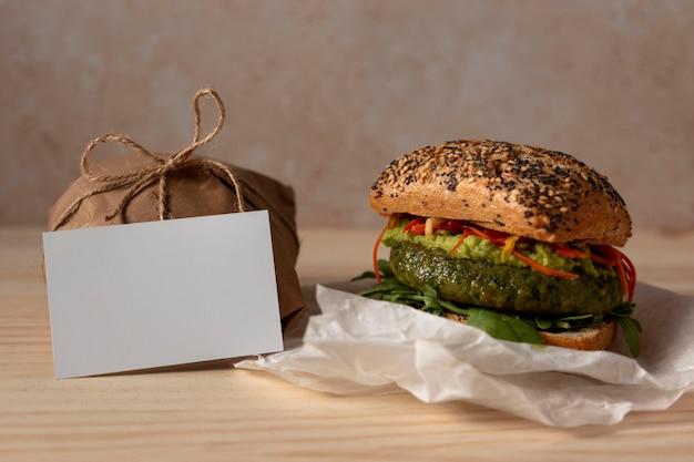 Hambúrguer de frente com pacote de entrega