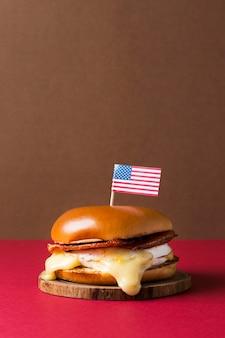 Hambúrguer de frente em peça de madeira com bandeira americana