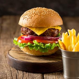 Hambúrguer de frente na tábua com batatas fritas