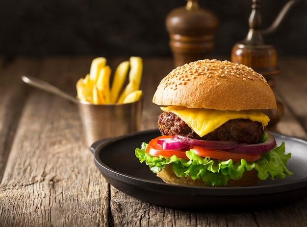 Hambúrguer de frente no prato com batatas fritas