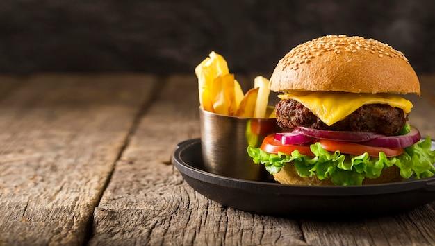 Hambúrguer de frente no prato e batatas fritas com espaço de cópia