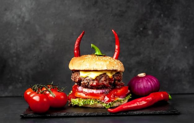 Hambúrguer de halloween em formato de abóbora com chifres de pimenta vermelha na parede de pedra