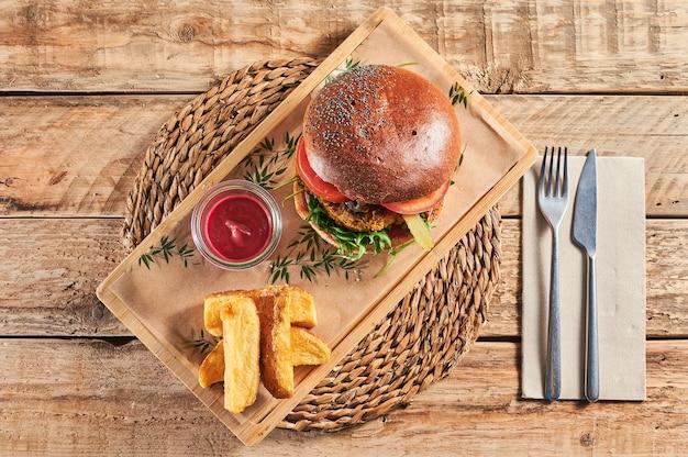 Hambúrguer de lentilha vegano pronto para comer com ketchup de beterraba servido em uma mesa rústica de madeira