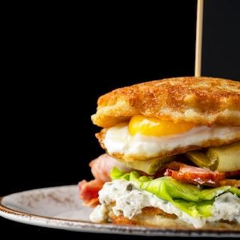 Hambúrguer de panquecas de batata com ovos fritos, bacon