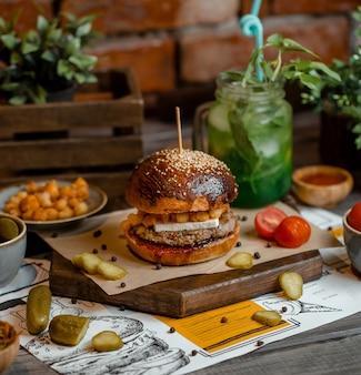 Hambúrguer de pão marrom com turshu em uma placa de madeira