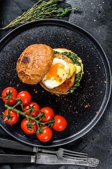 Hambúrguer de peixe caseiro com filé de bacalhau, ovo e espinafre em um bolo de brioche. superfície preta. vista do topo