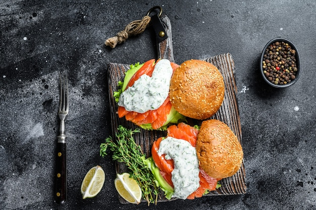 Hambúrguer de peixe com salmão salgado, abacate, molho de mostarda, pepino e salada de iceberg
