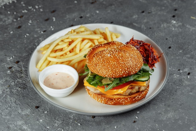 Hambúrguer de peru em um pão com queijo, alface, tomate e pepino fresco. hambúrguer com costeleta de carne de peru em um fundo cinza com molho de batata frita e salada.