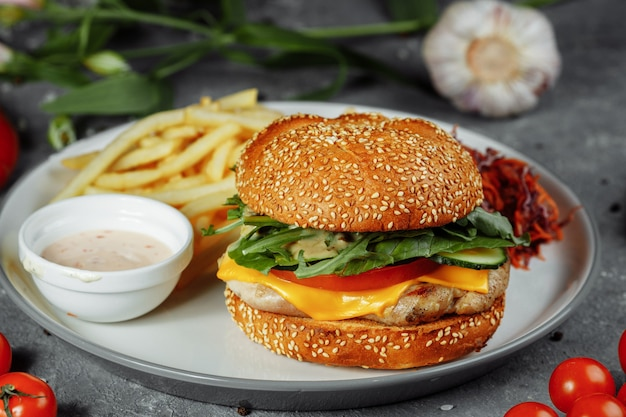 Hambúrguer de peru em um pão com queijo, alface, tomate e pepino fresco.