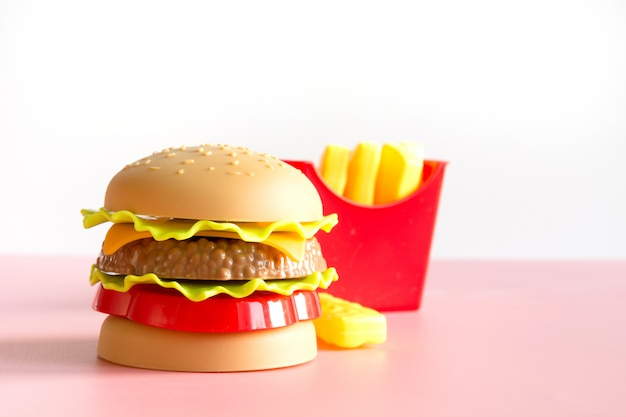 Hambúrguer de plástico, salada, tomate, fritura de batata com rosa.