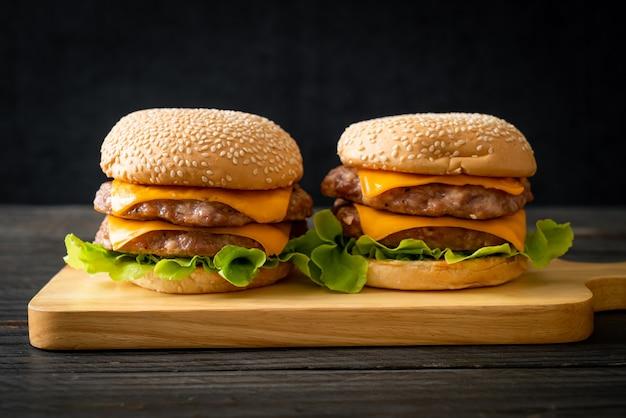 Hambúrguer de porco ou hambúrguer de porco com queijo na tábua de madeira
