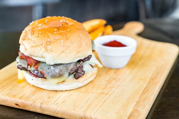 Hambúrguer de queijo bacon com carne na placa de madeira no restaurante