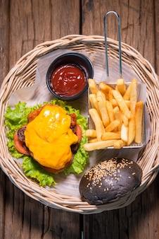 Hambúrguer de queijo de frango e churrasco, com cebola, tomate e alface, servido com batatas fritas e molho de tomate