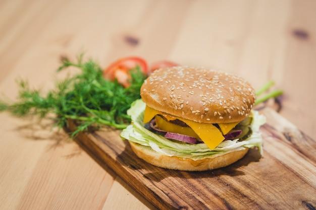 Hambúrguer de queijo de frango em fundo de madeira com espaço de cópia no topo