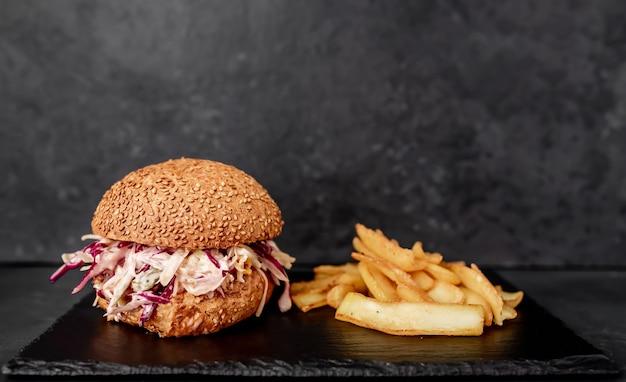 Hambúrguer de rabada com batata frita de repolho em uma mesa de pedra